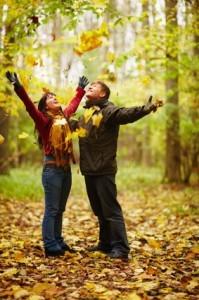 Autumn - Happy couple enjoying falling leaves