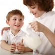 Mother pours milk to son