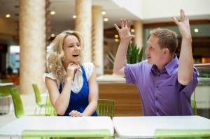 Young debating or talking couple inside mall sitting near the ta